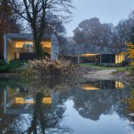 Forest house of stone and glass is reflected back in water