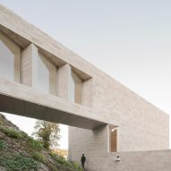 Bridge links historic German museum to travertine-clad extension