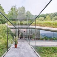Glass corridor connects underground concrete extension to house in Spain