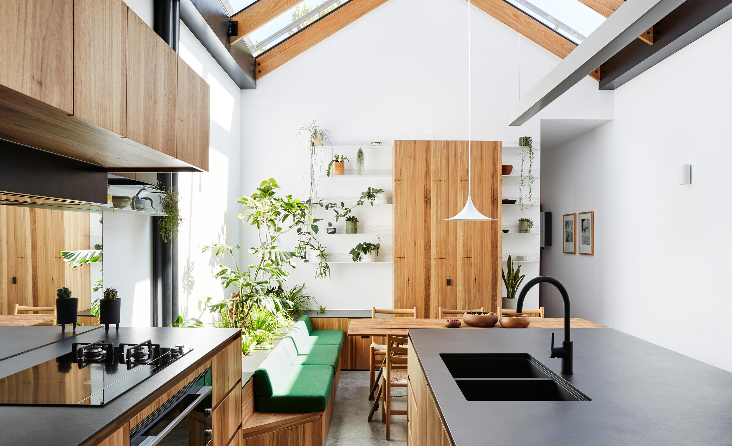 A white kitchen with plants and wooden cabinetry