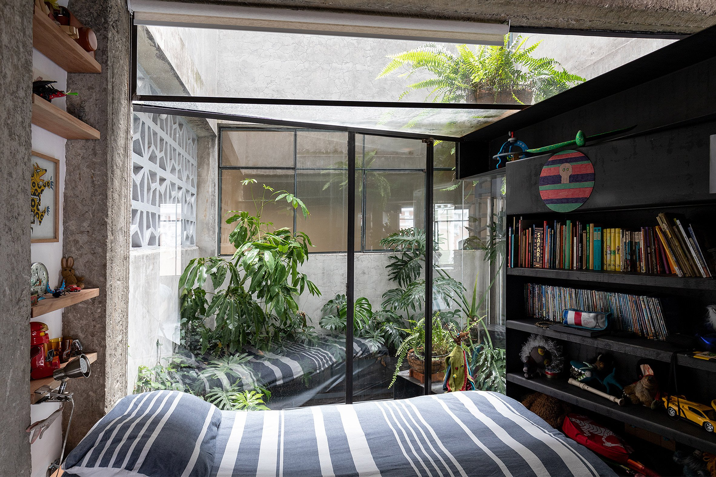 A bedroom overlooking a plant-filled courtyard