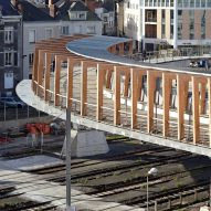 Dietmar Feichtinger Architectes designs gently curving timber bridge over train tracks in Angers
