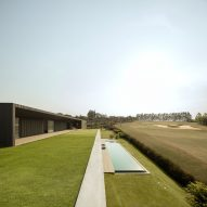 Green roof blends Brazilian house by Studio Arthur Casas with nearby golf course