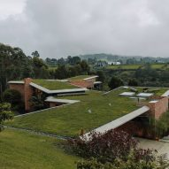 Casa Carmen's green roofs merge with hill and forest in Colombian neighbourhood