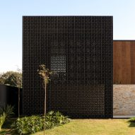 Perforated black blocks screen Cobogós House in Brazil by MF+ Arquitetos