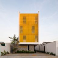 Yellow grates filter light into apartment building by Laurent Troost Architectures