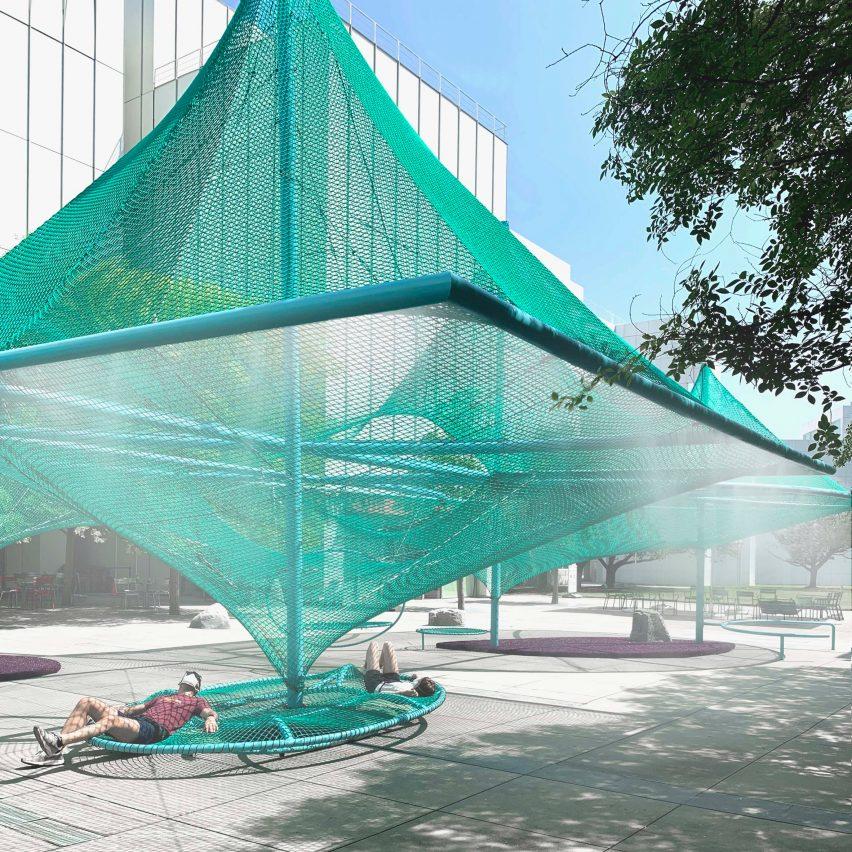 Green net shades hammocks and bird feeders in Murmuration by SO-IL