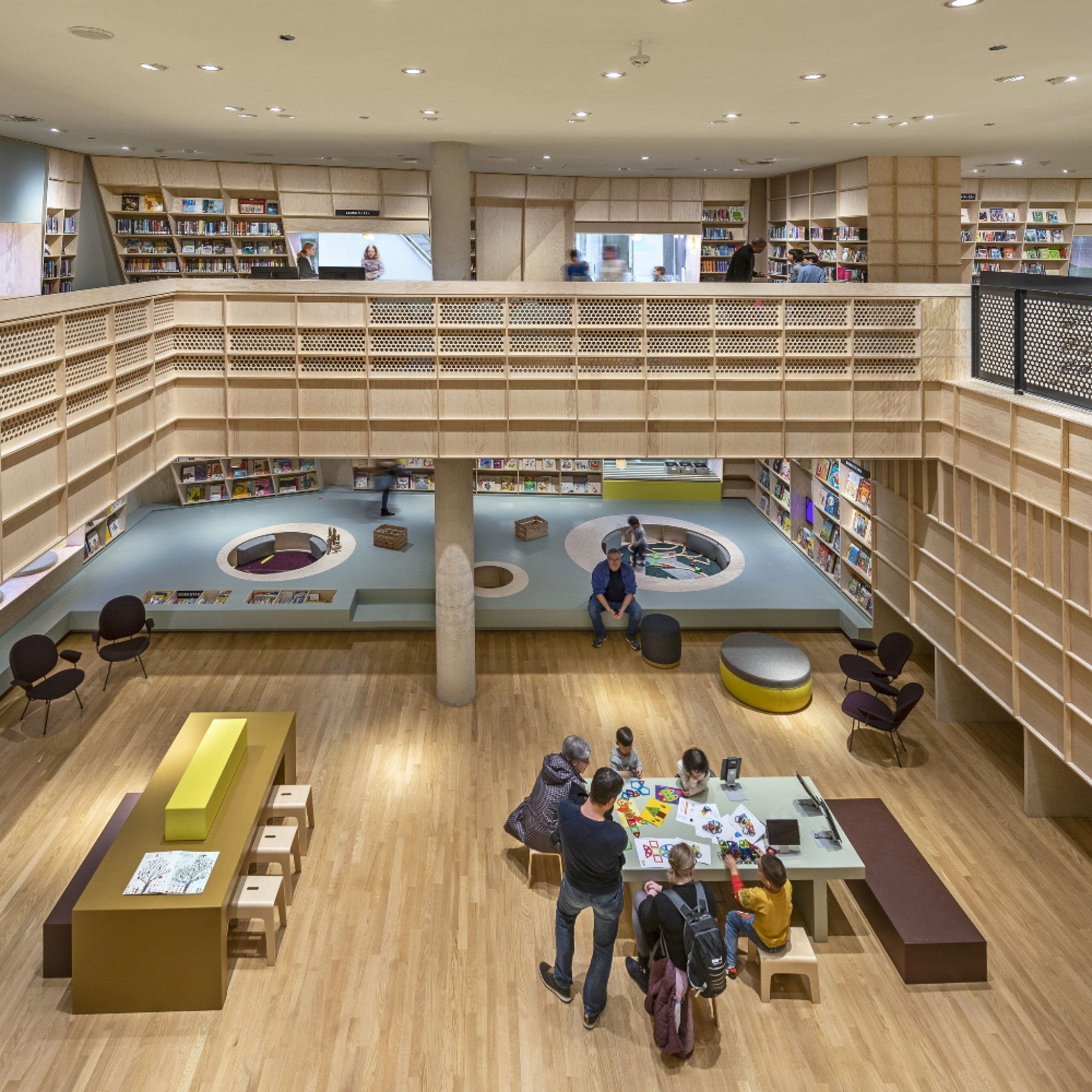 The interior emphasizes the architecture and offers space for more than just books: the children can curl up in the window niches, play in a chill net or experiment with techniques