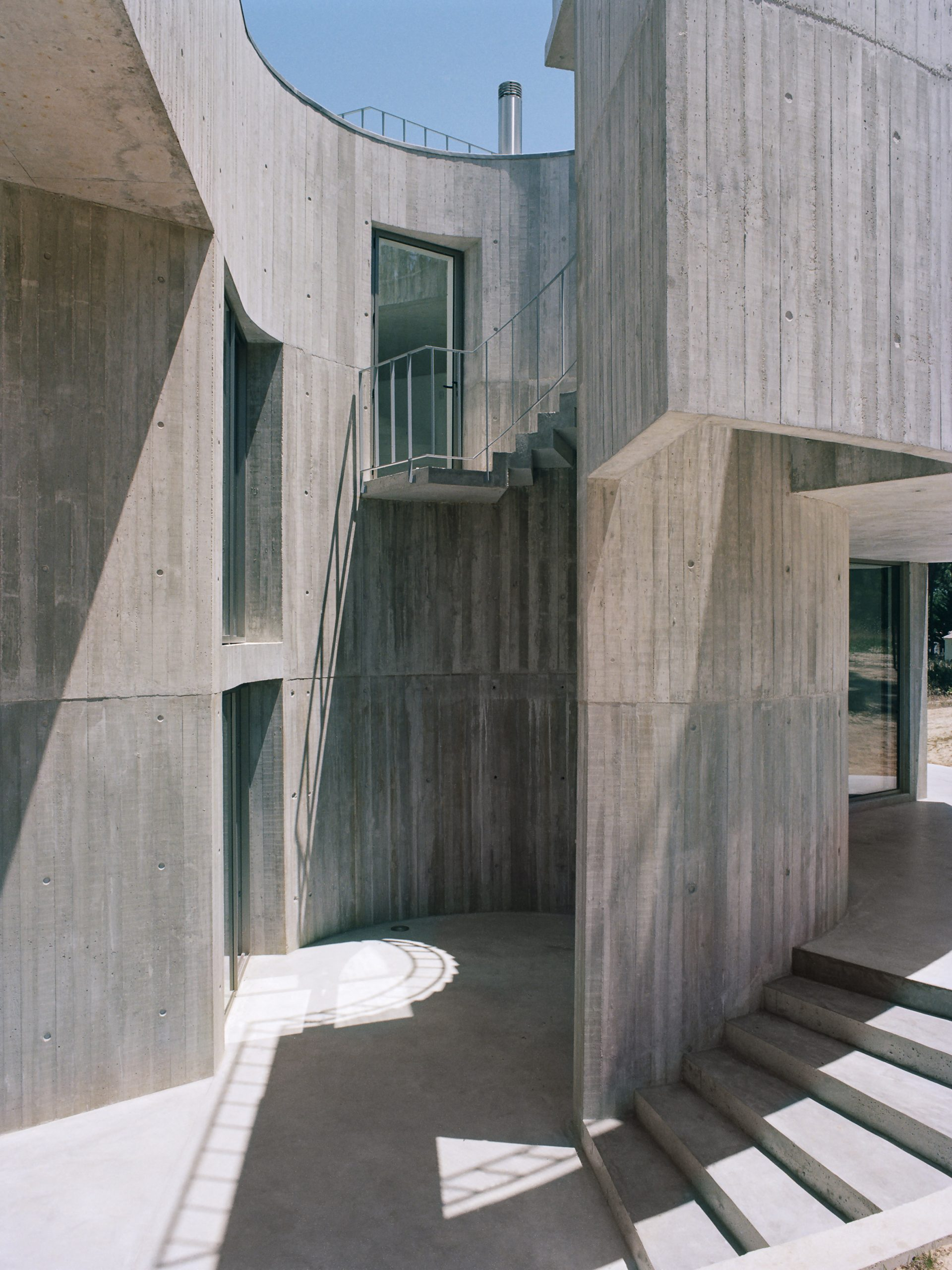 Concrete patio of Trefoil House by Double O Studio