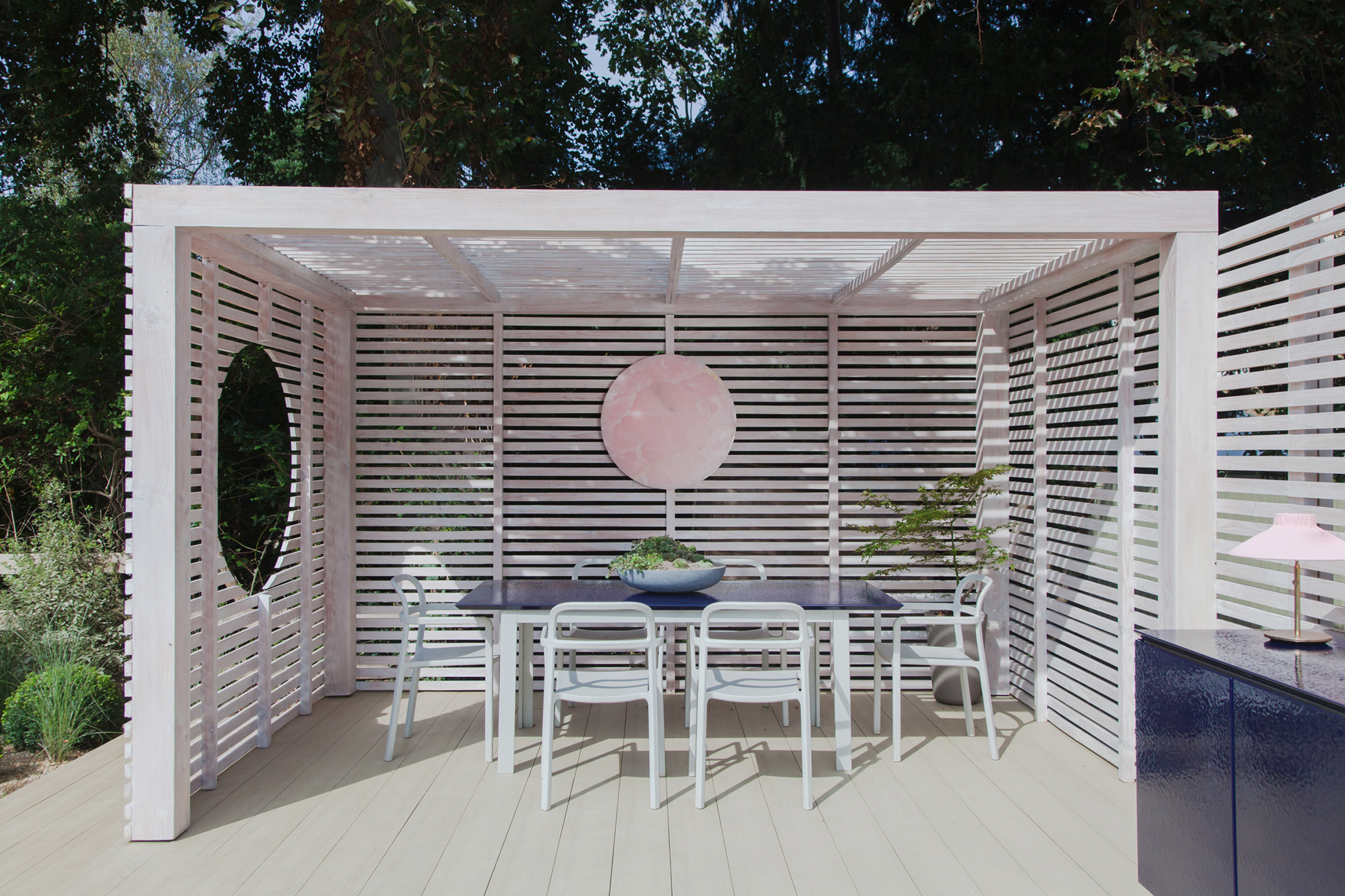 White-painted garden pavilion with dining area