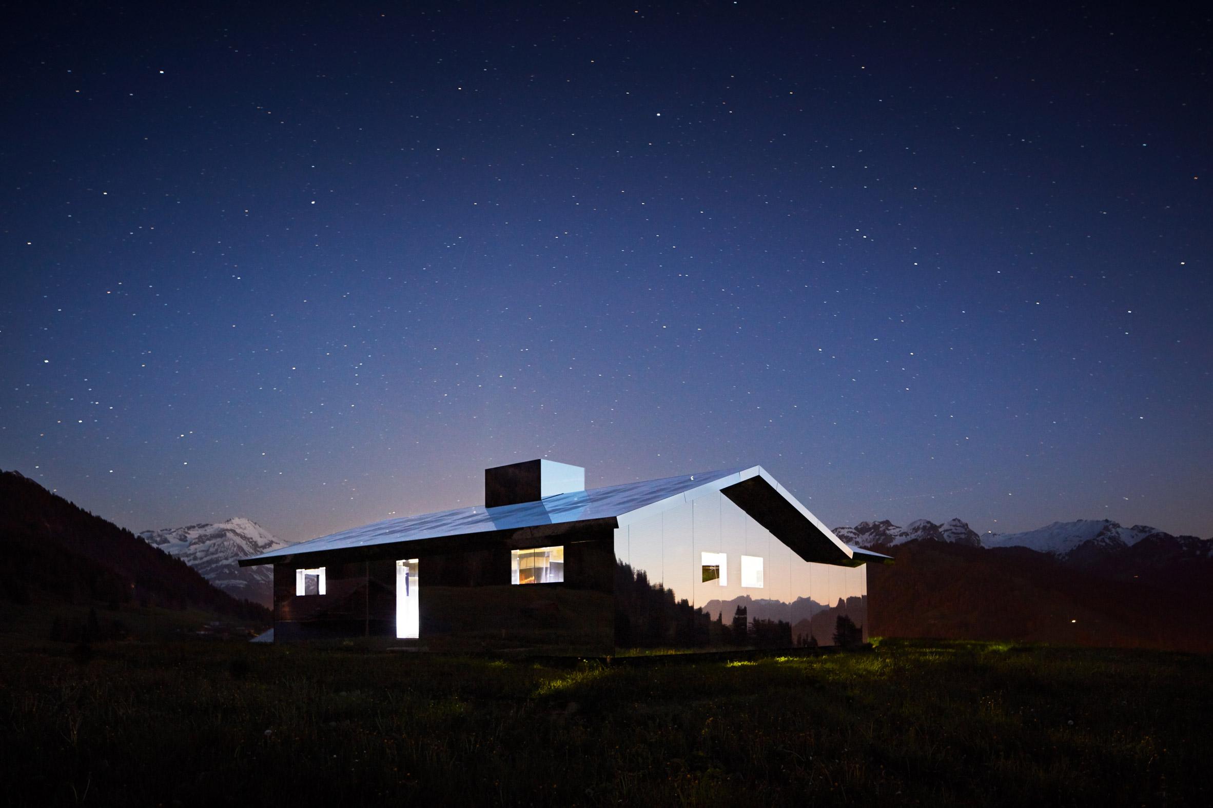 Mirage Gstaad mirrored building art installation by Doug Aitken in Switzerland at night