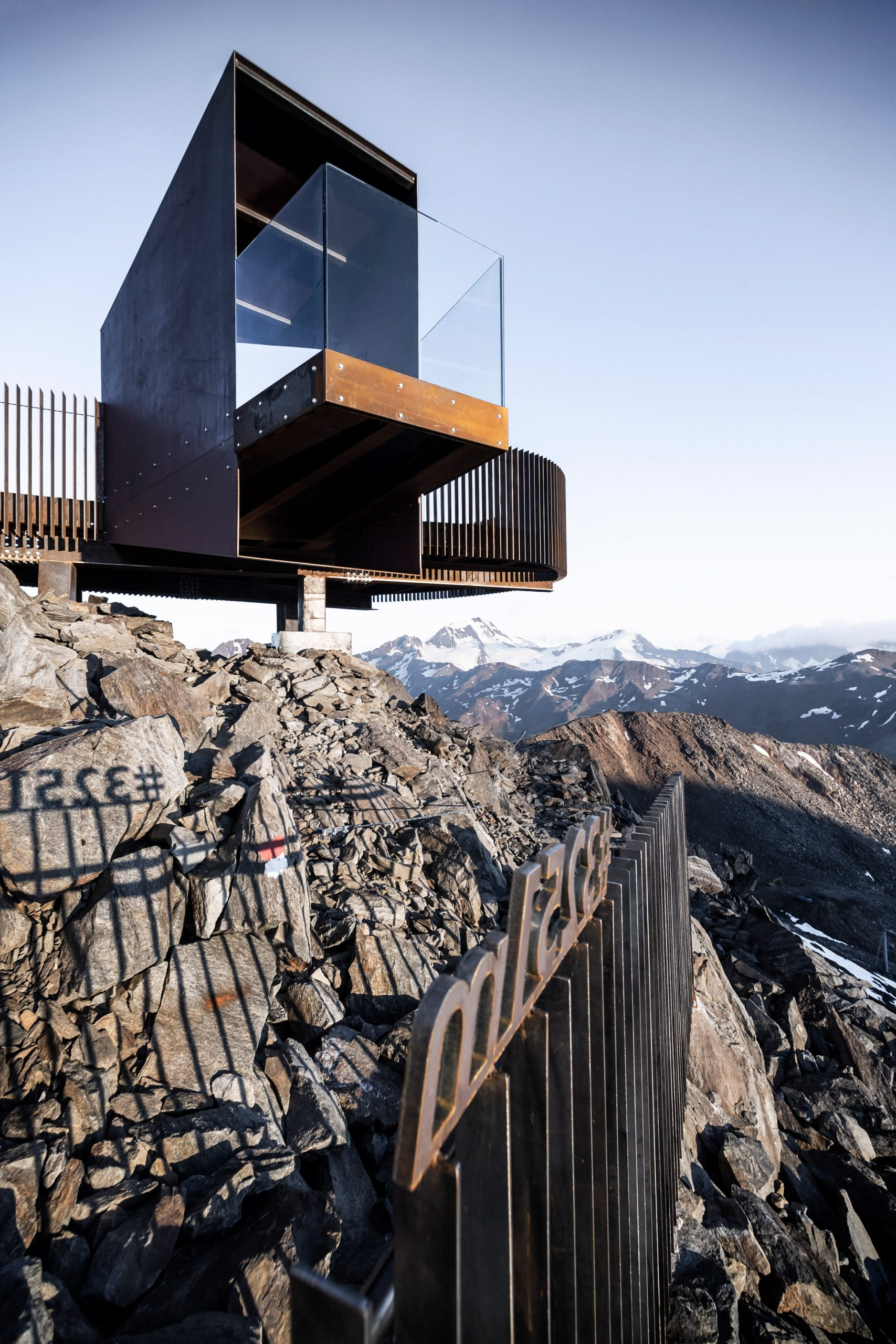 Viewing platform made of weathering steel and glass projects over Italian Alps