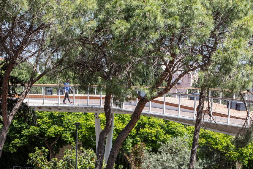 Eye-level view of the Technion Entrance Gate bridge amongst the trees