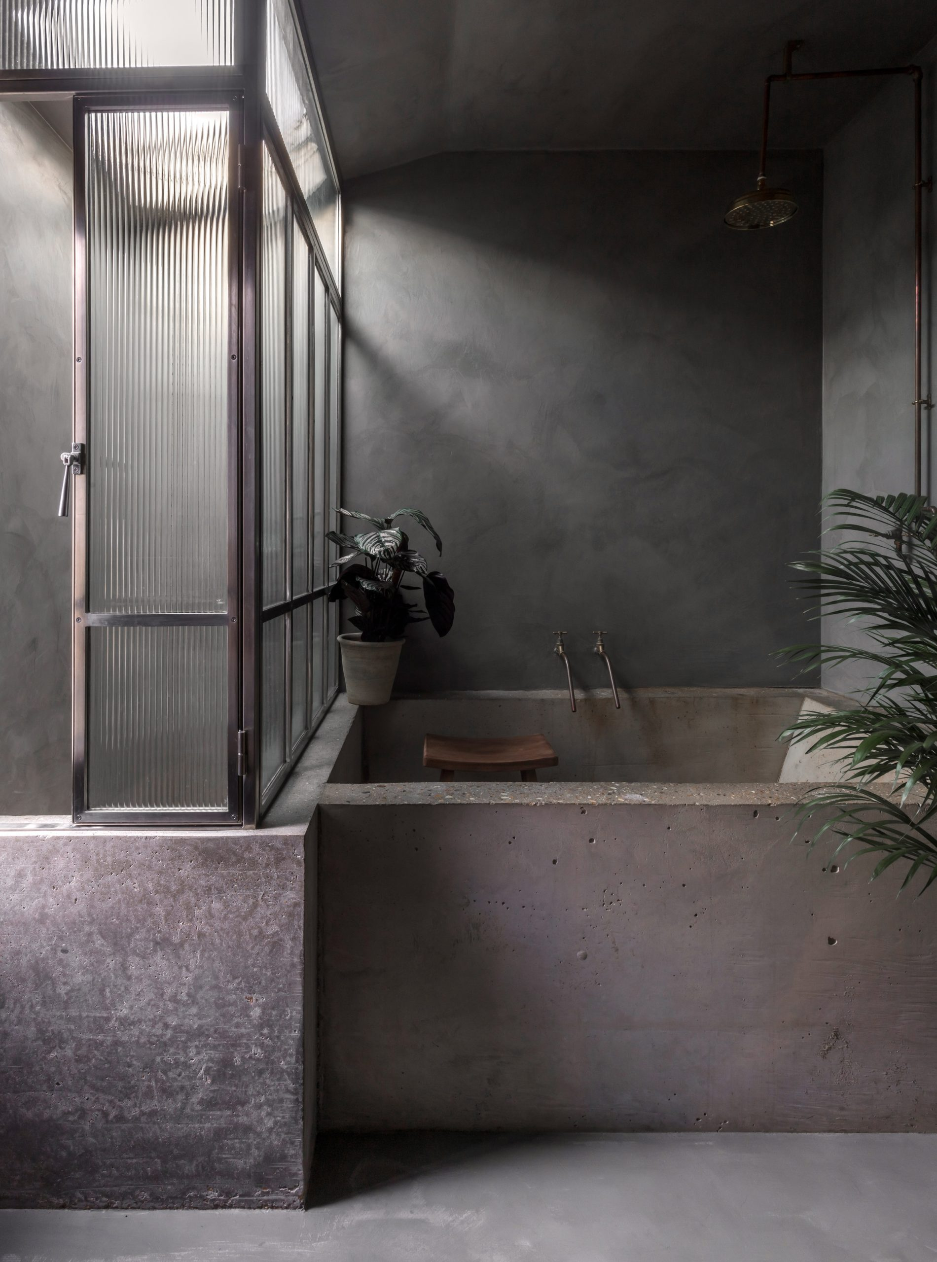 Concrete bath and Crittal screen in bathroom of Untiled House extension by Szczepaniak Astridge in London