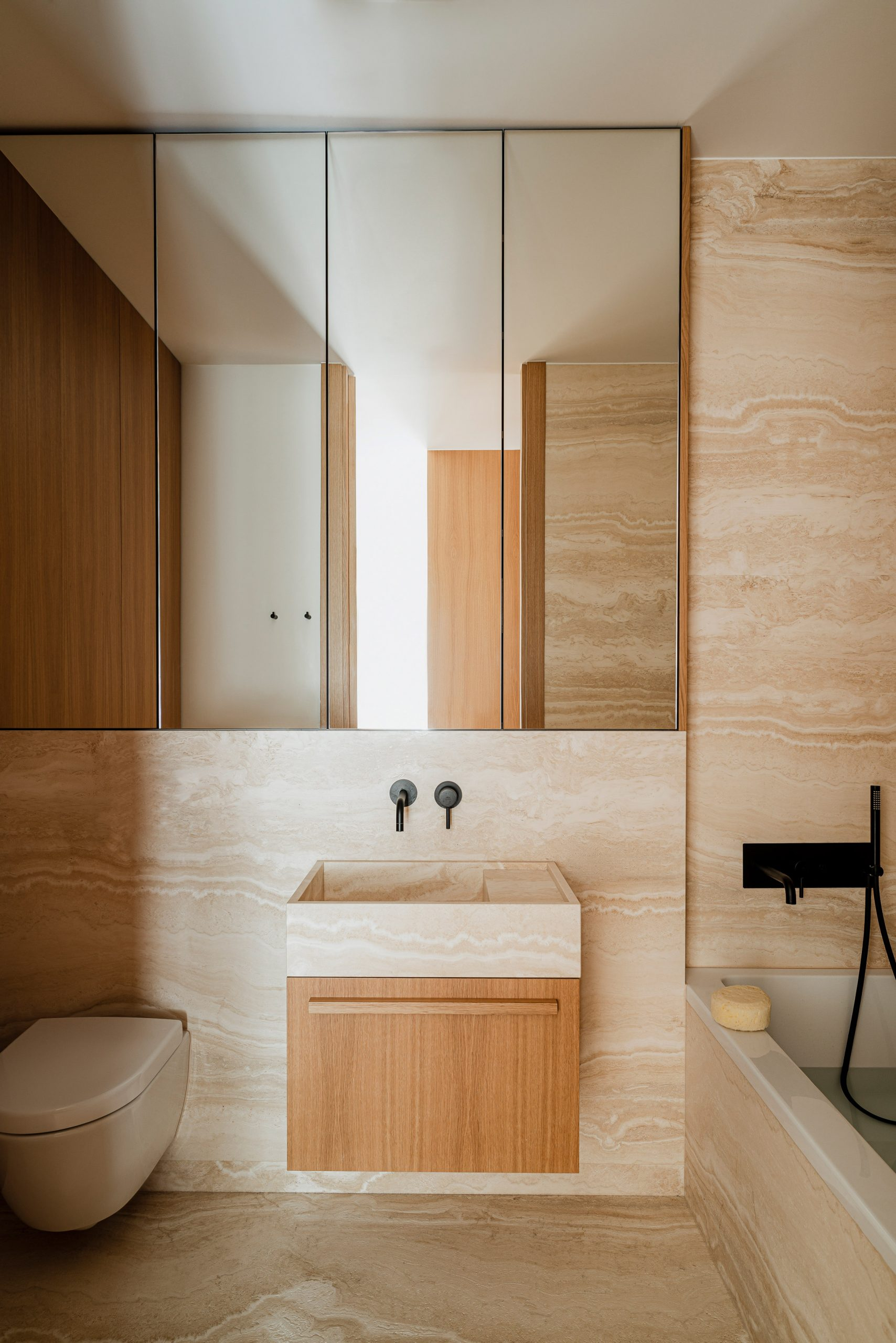 Travertine marble bathroom of Botaniczna Apartment by Agnieszka Owsiany Studio