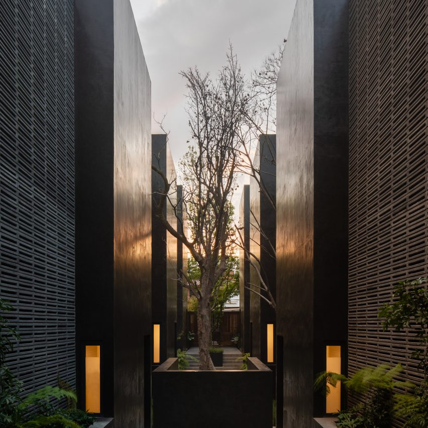 Black monolithic volumes and concrete latticework form Carrizal houses in Mexico City