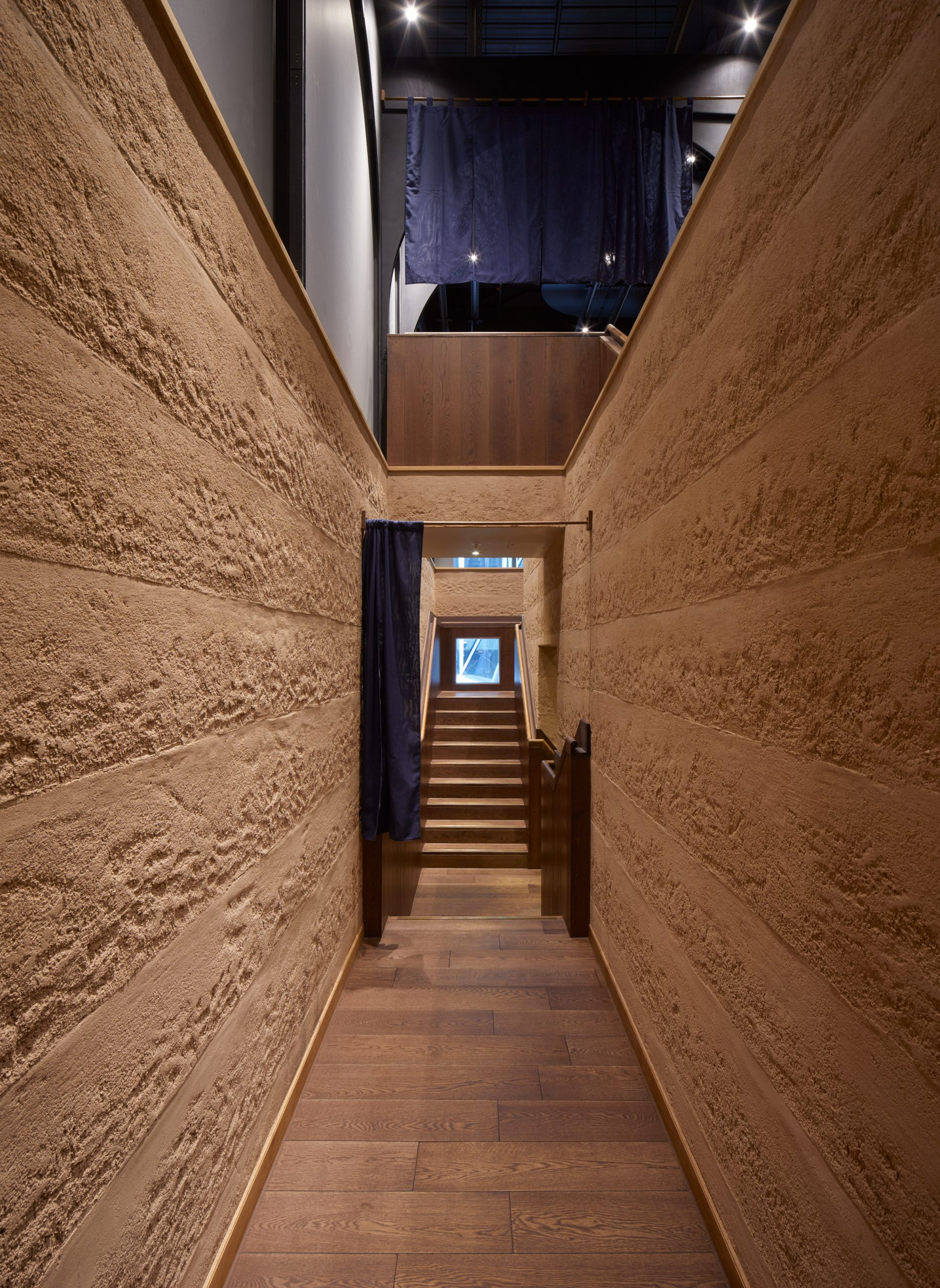 Corridor with Rammed Earth Finishes clay plaster walls by Clayworks