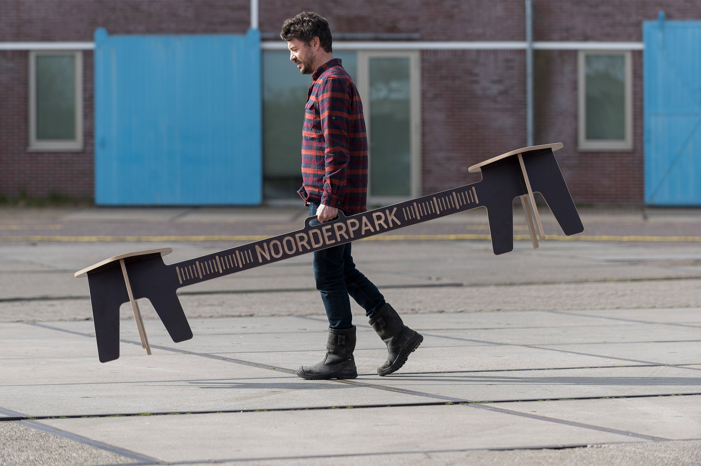 The designer carrying Corona Crisis Kruk, a social distancing bench by Object Studio