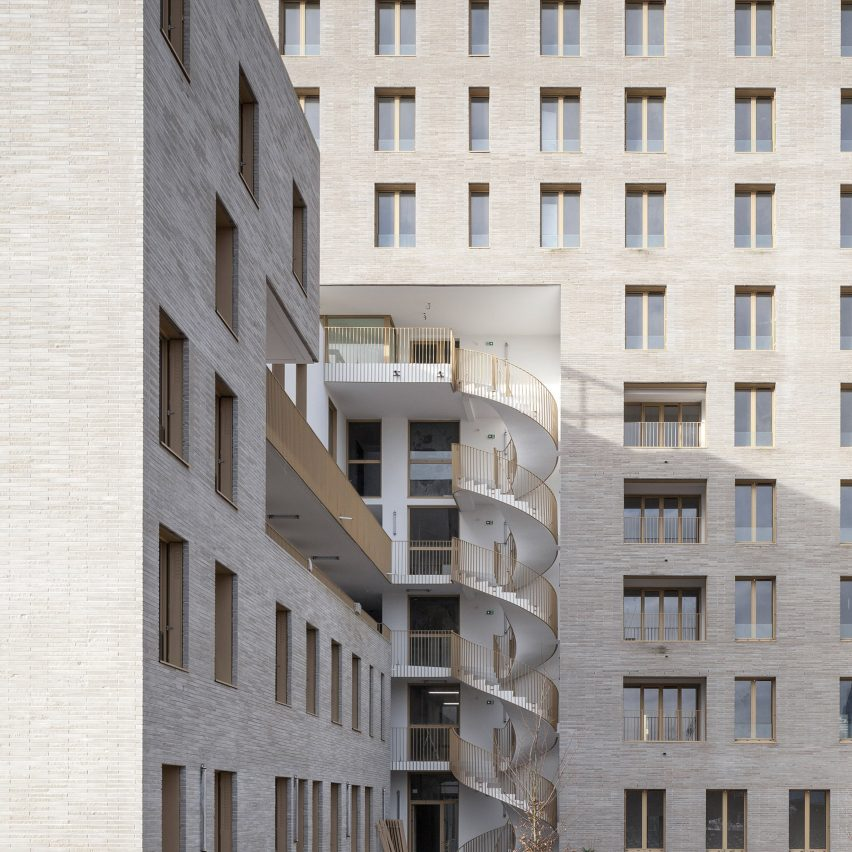 Spiral staircase twists through Zellige apartment complex by Tecto?ne and Tact Architectes