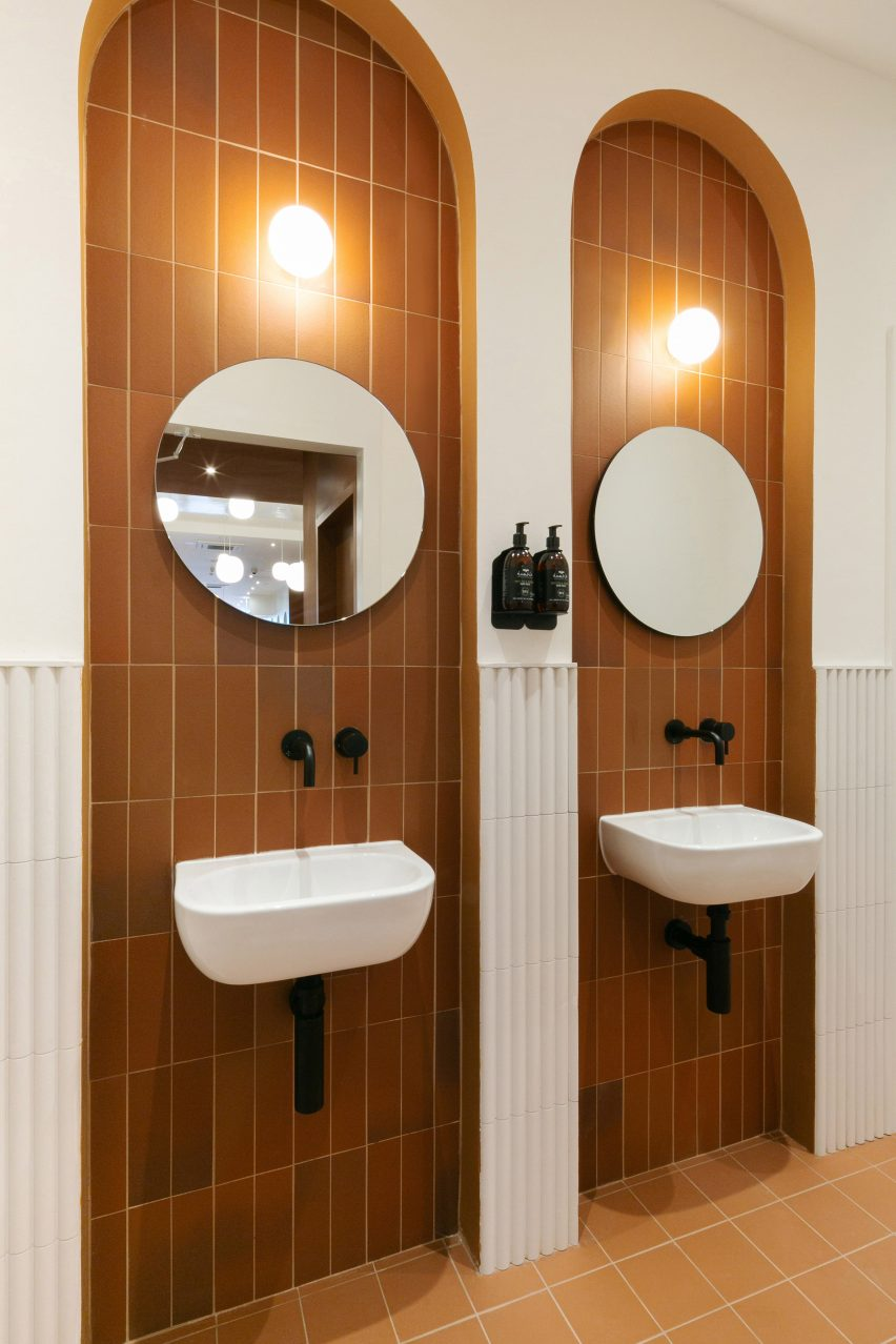 Bathrooms inside Beam cafe in London feature terracotta tiles