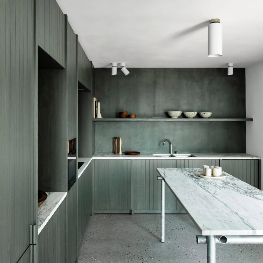 Seaweed-coloured kitchen with marble worktops