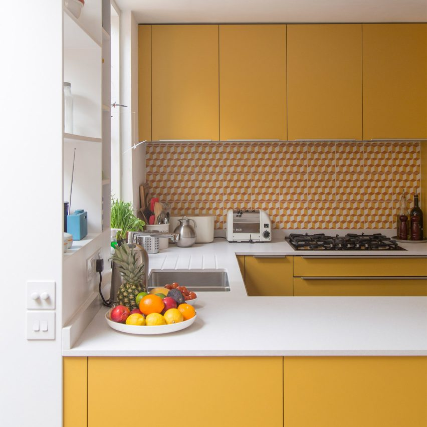 Mustard yellow kitchen with orange splashback tiles