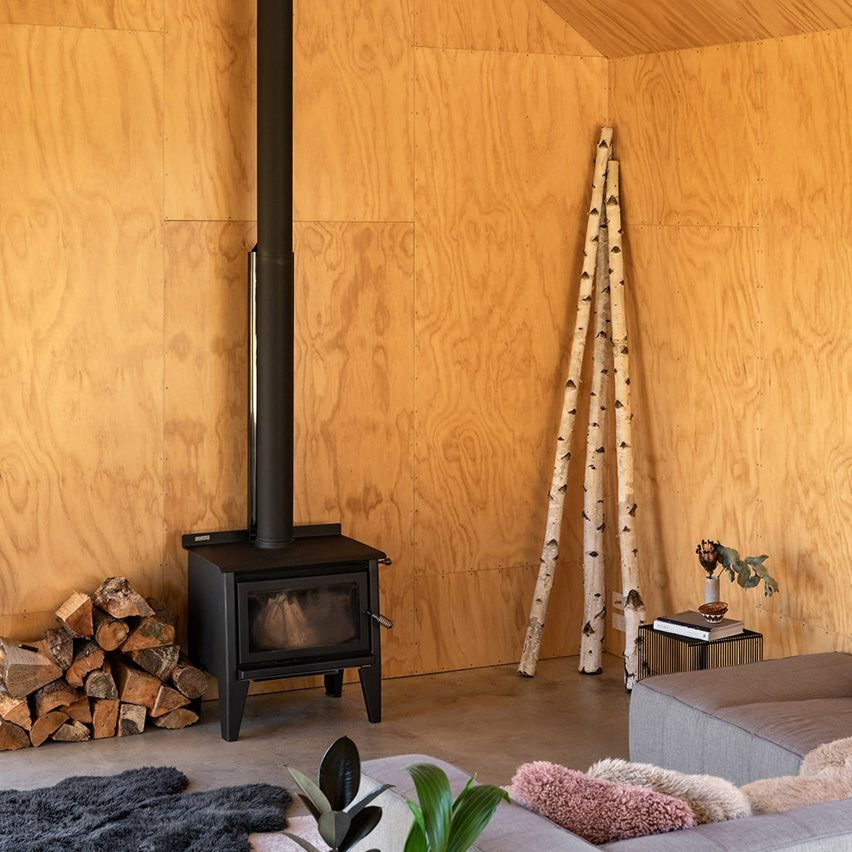 Plywood-lined living room with wood-burning stove
