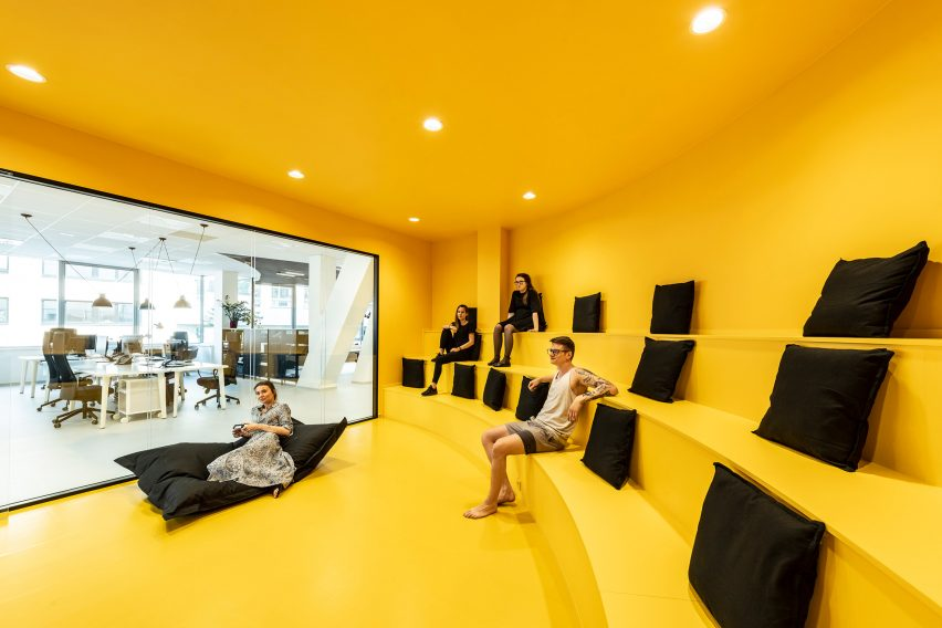 Yellow amphitheatre seating inside the office for DDB Prague by B2 Architecture, Czech Republic