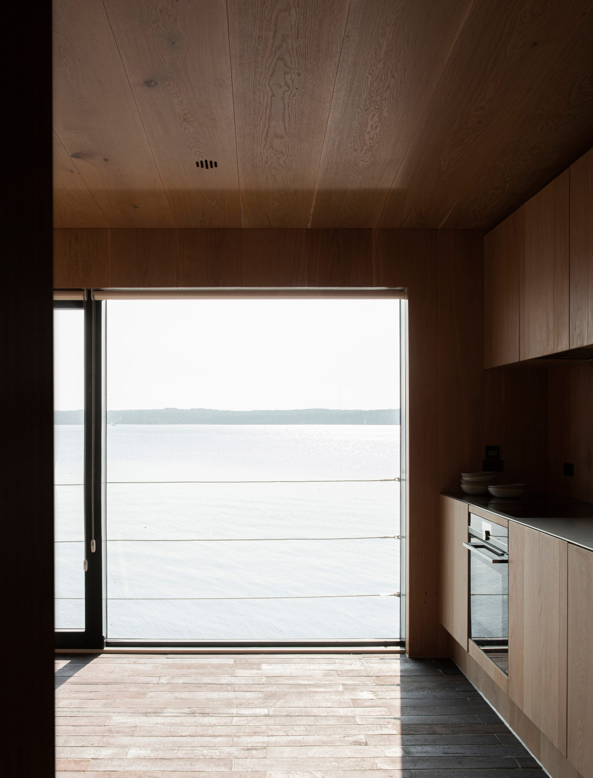 Kitchen of Fjord Boat House by Norm Architects has lake views