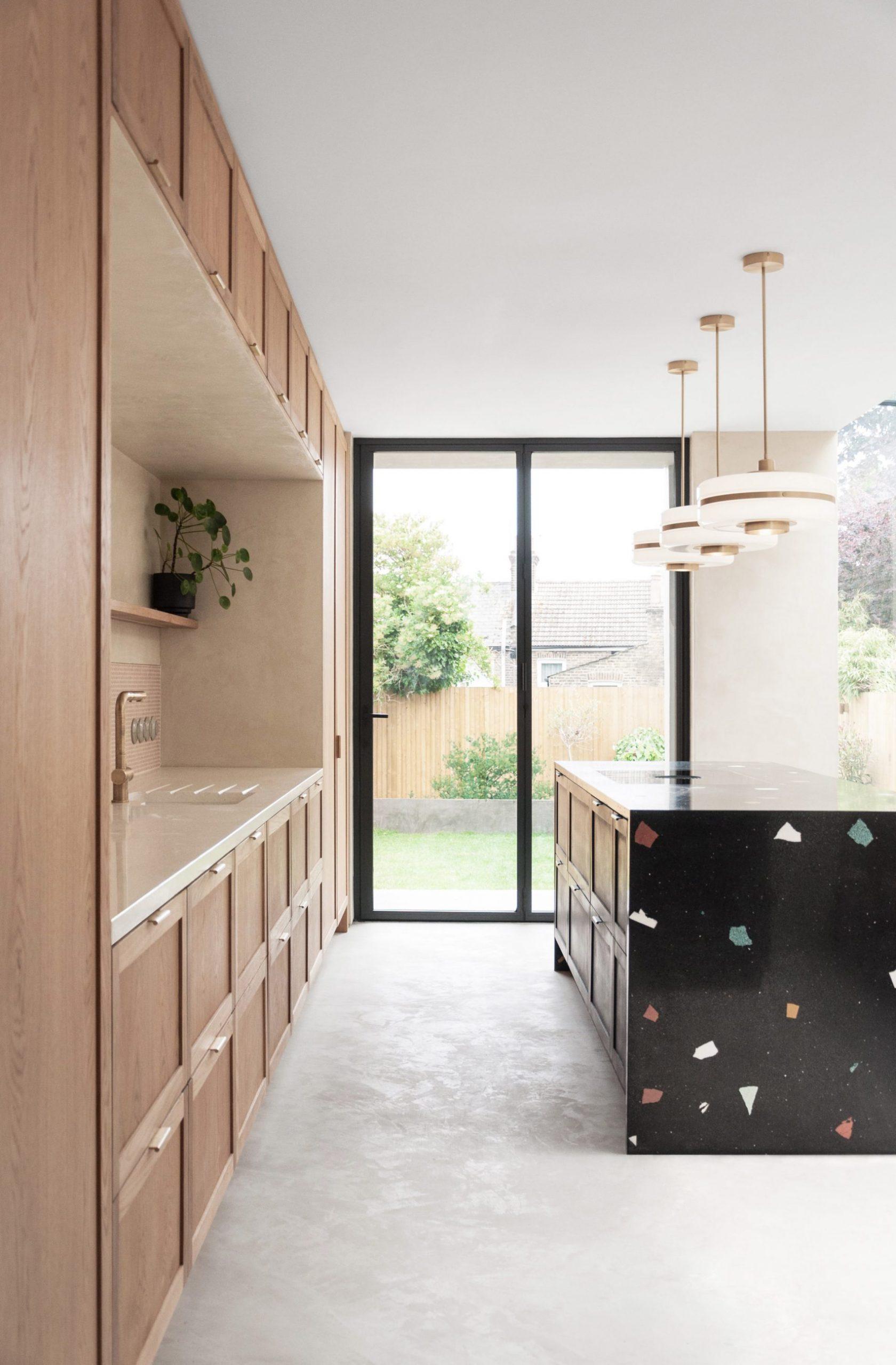 Black kitchen island with oversized terrazzo