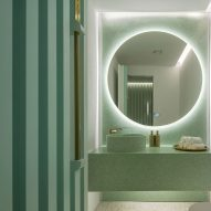 Grooved green walls feature inside Infinity Wellbeing spa in Bangkok