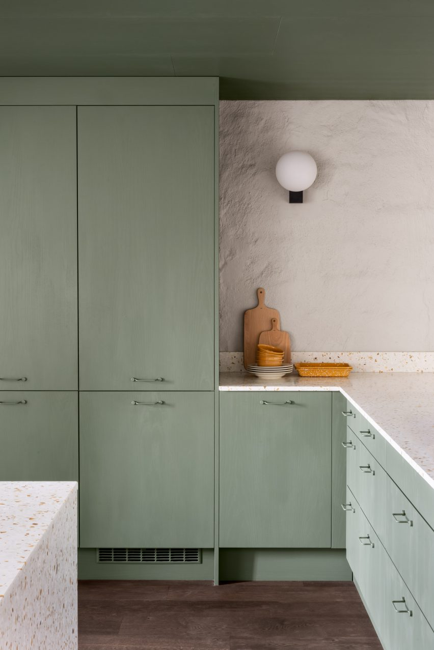 Pale green kitchen with terrazzo tops