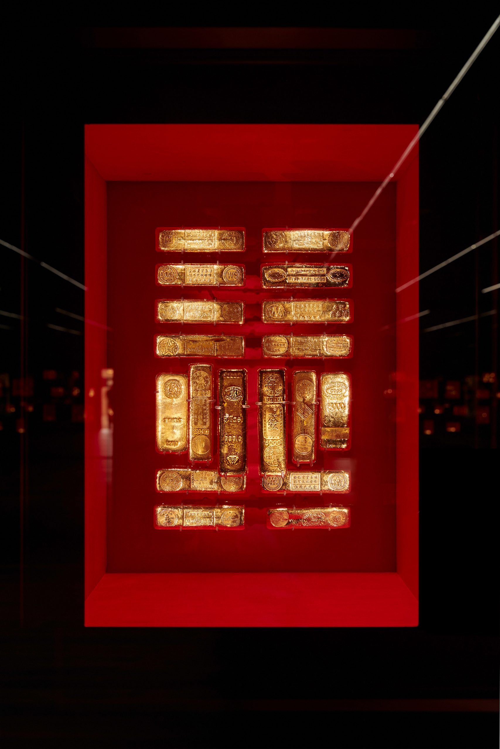 Gold bullion against red silk The Rothschild Collection displayed by Pfarré Lighting Design at the Goldkammer Museum in Frankfurt