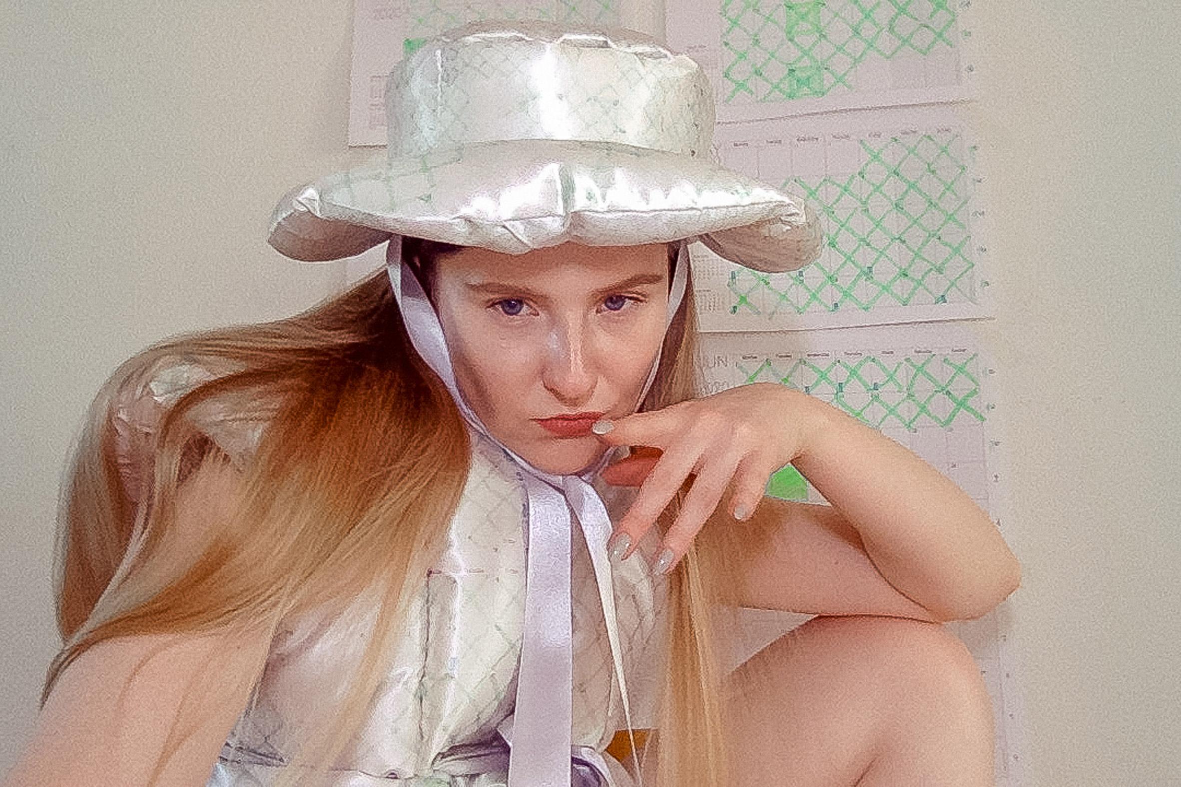 Santa Kupča wearing her Hesitant to RSVP duvet-style garment and hat