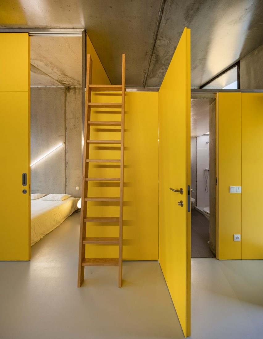 Yellow walls inside VDC modular prefabricated concrete housing by Summary in Portugal