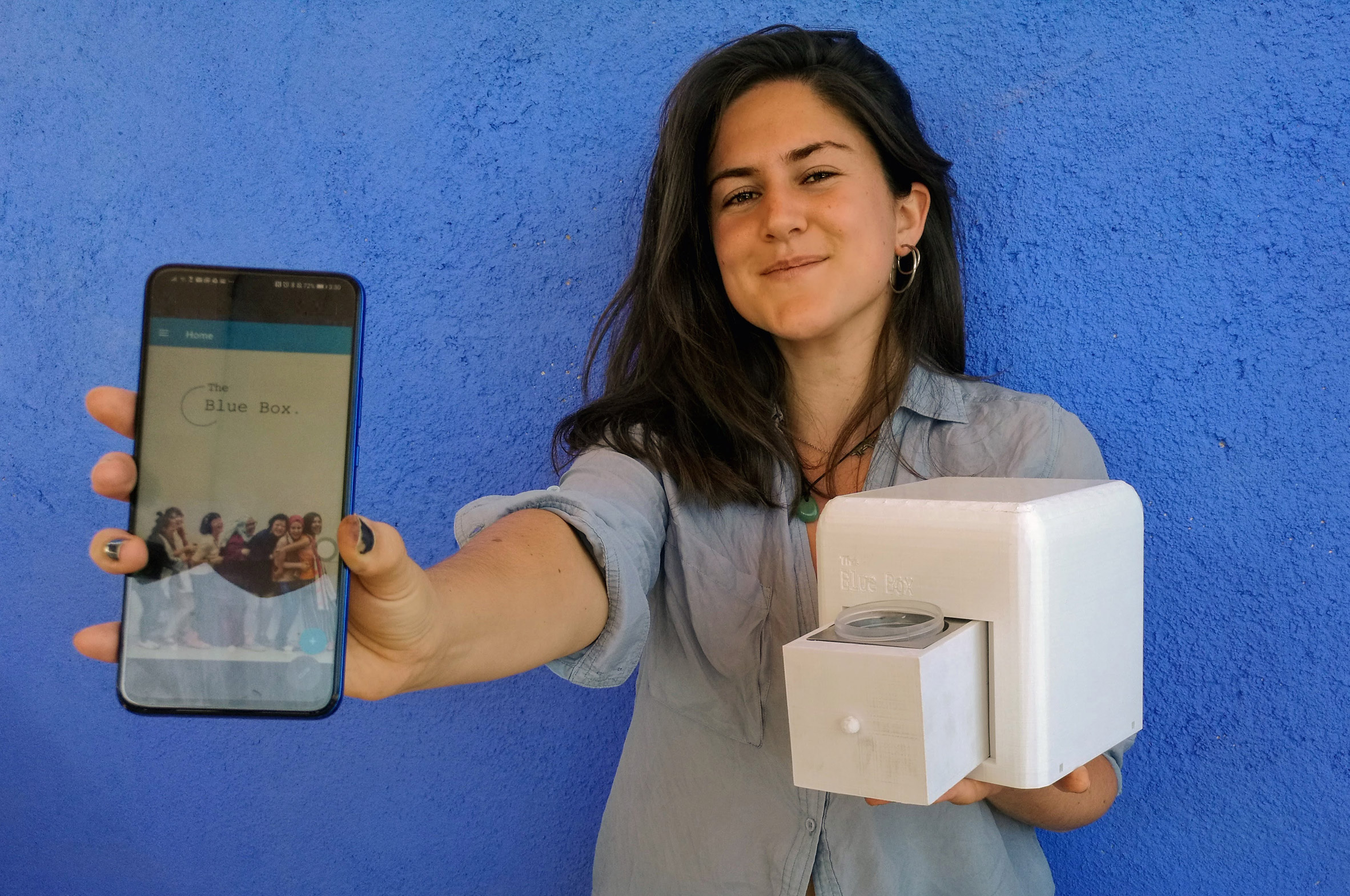 Judit Giró Benet holding The Blue Box, an at-home breast cancer testing kit