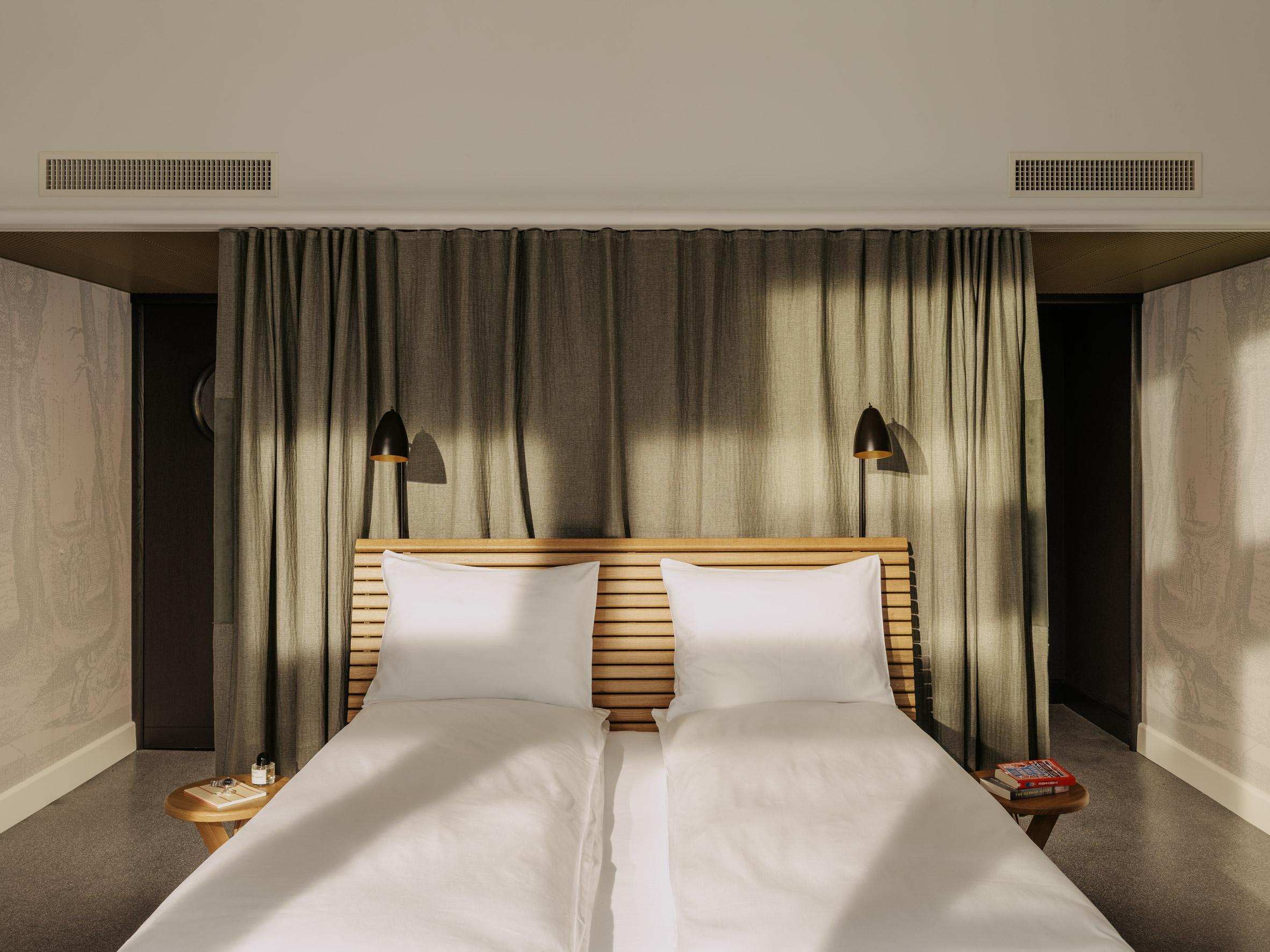 Bed with oak-slatted headboard in hotel bedroom
