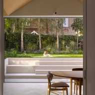 Glass doors open out to the garden in Hampstead House by Dominic McKenzie Architects