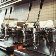 Coffee details behind the main black monolithic terrazzo bar