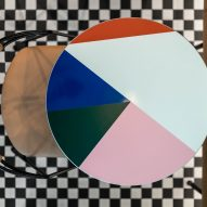 Circular tables covered in coloured laminate from above showing checkerboard mosaic floor