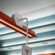Italian signs illustrating where to pay and order slide along an orange painted steel beam above the bar