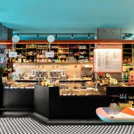 The main black monolithic terrazzo bar showing an orange painted steel beam above the bar