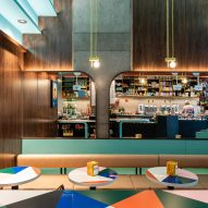 The main black monolithic terrazzo bar reflected in the curved mirrors