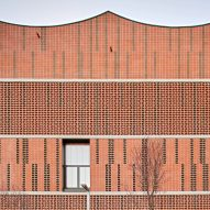 Assorted bricks give texture to facade of Camp del Ferro sports centre in Barcelona