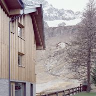 The exterior of a stone and wood-clad chalet by LCA Architetti