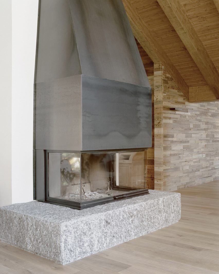 A fireplace inside an Italian chalet by LCA Architetti