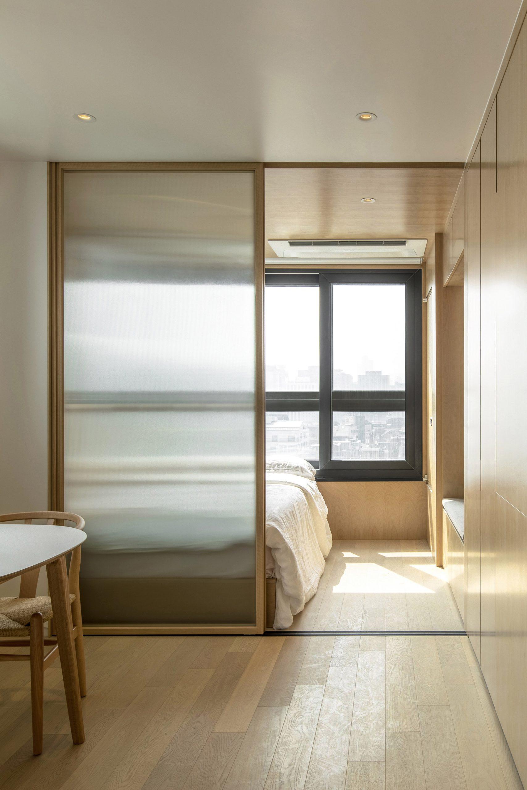 Wood-clad bedroom with interior window