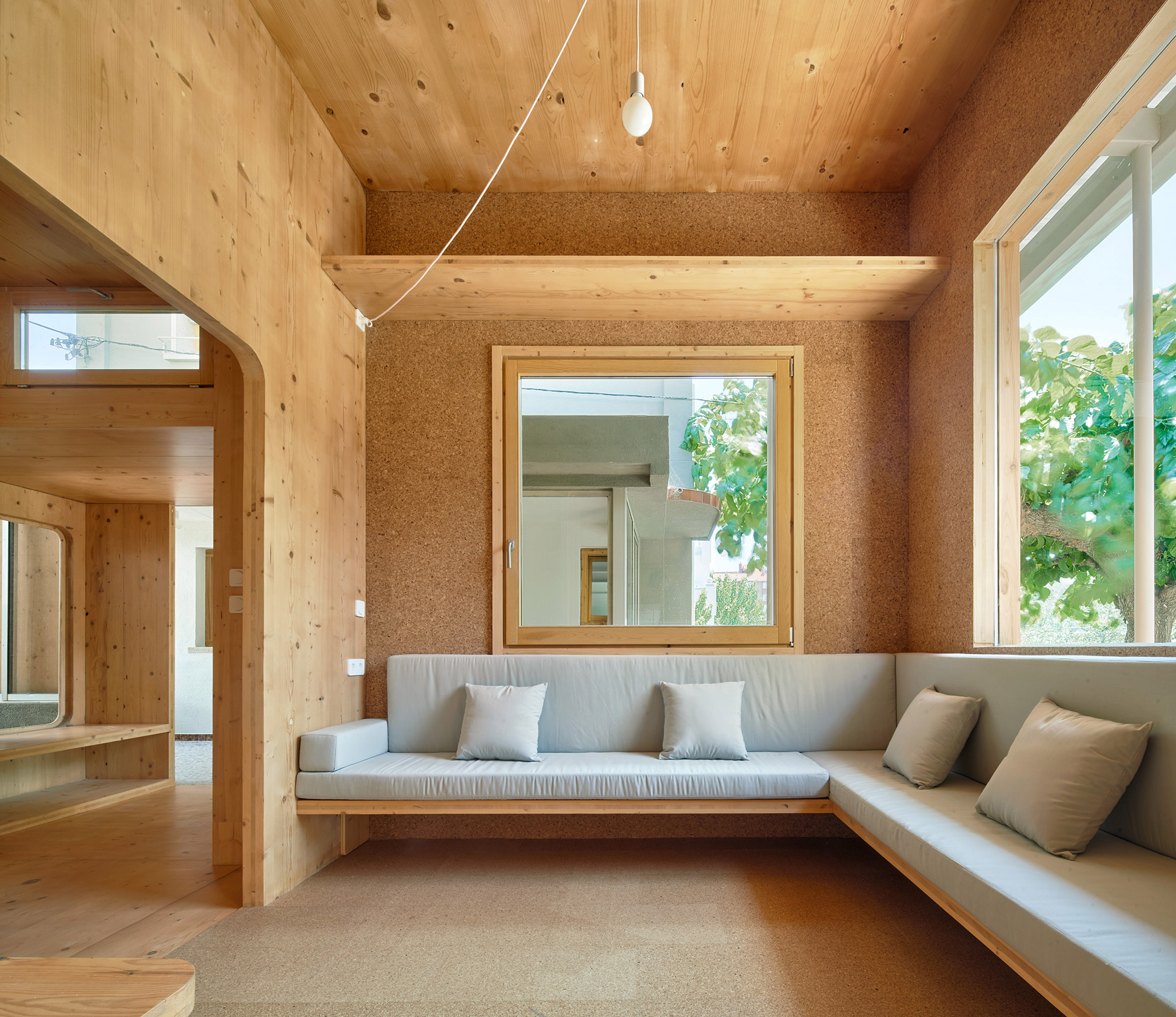 Built in sofa with pale upholstery sits below large square windows by Aixopluc