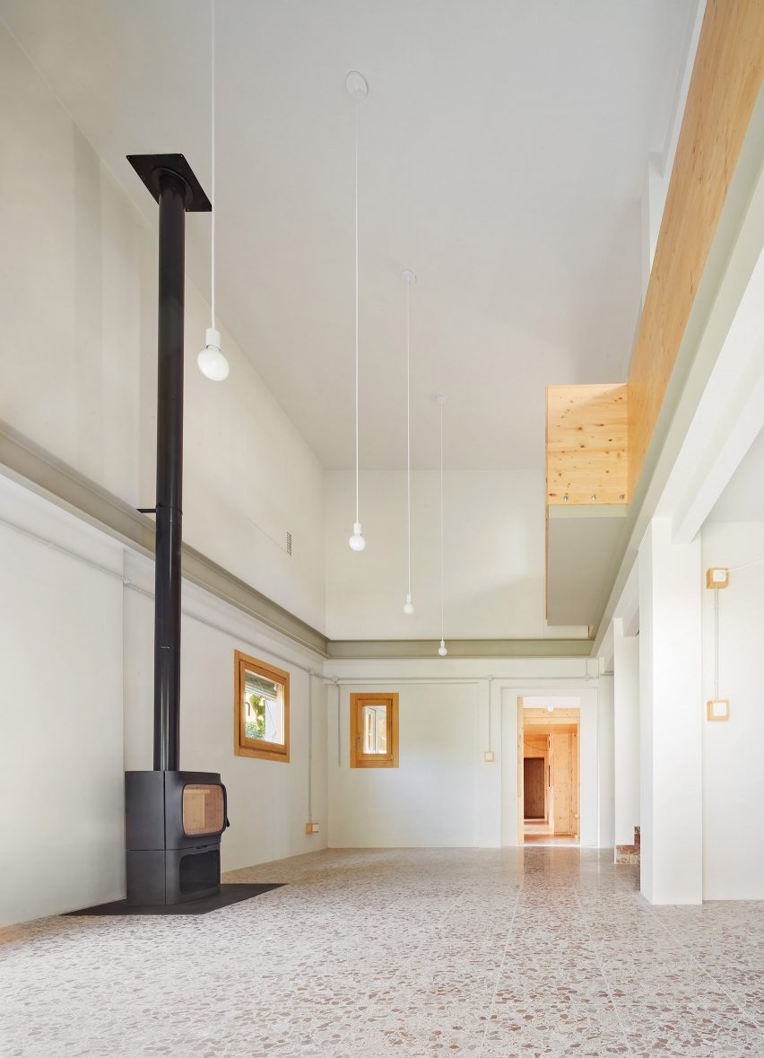 Pendant lighting fills the room and a wood burner sits a top the terrazzo floor