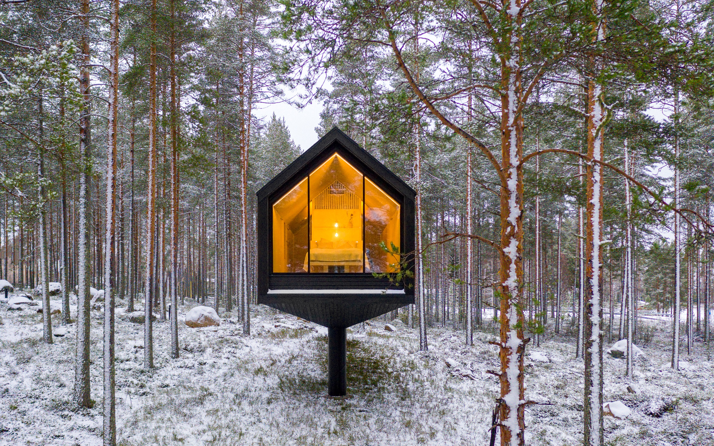 A black cabin elevated on a column in Finnish woodland
